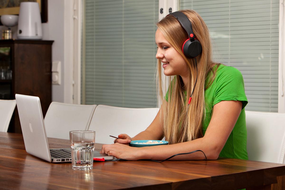 Tyttö istuu pöydän ääressä tietokoneen edessä.