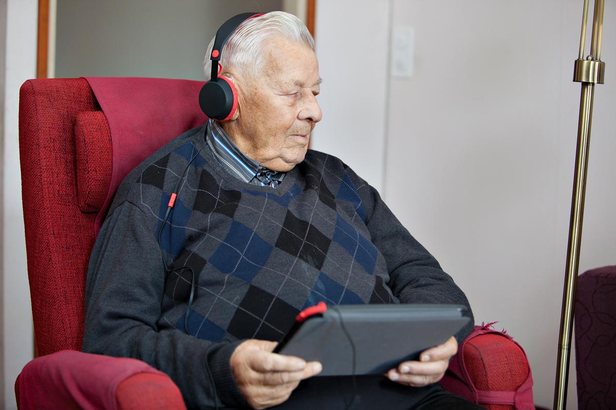ikääntynyt mies istuu nojatuolissa tabletti kädessään kuulokkeet korvissaan.
