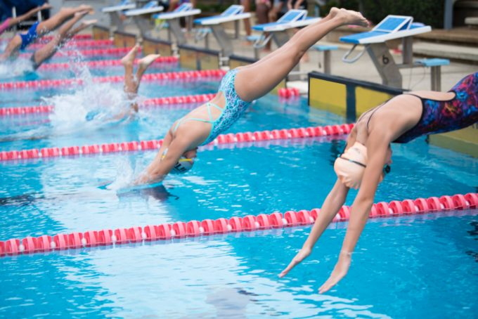 Kilpauimareita hyppäämässä veteen uimahallissa.