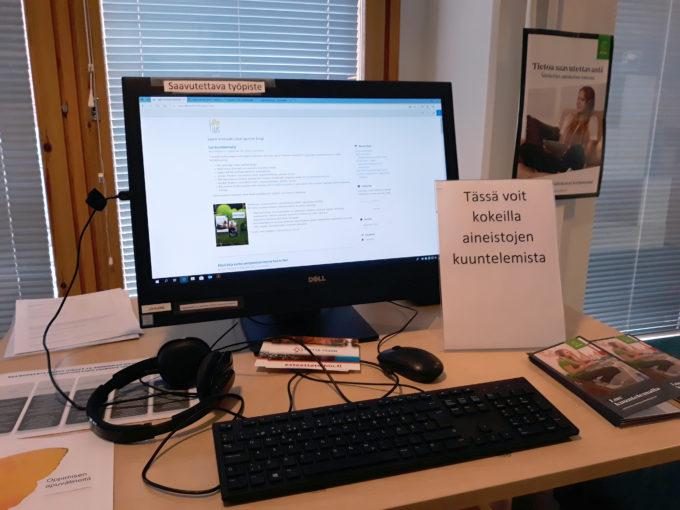 Tietokone ja kuulokkeet, joiden edessä kyltti Tässä voit kokeilla aineistojen kuuntelemista.