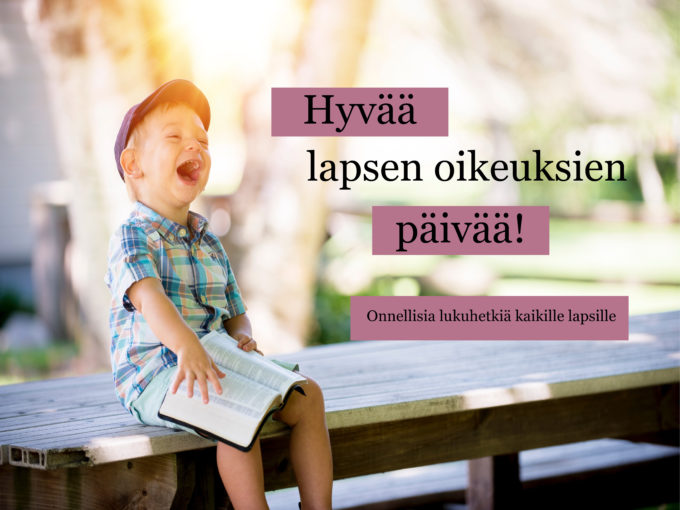 Pieni poika nauraa avoin kirja sylissään.