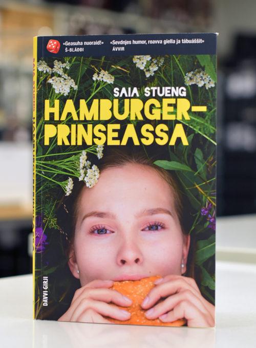 Pohjoissaamenkielinen kirja Hamburgerprinseassa. Kirjan kannessa tyttö makaa niityllä ja syö hampurilaista.