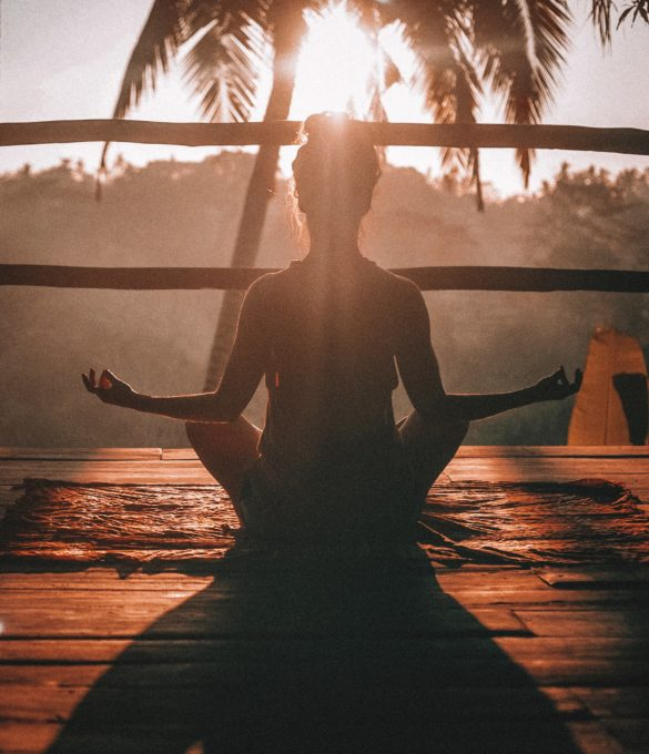 Nainen istuu lootus-asennossa meditoimassa aurinkoisella parvekkeella.