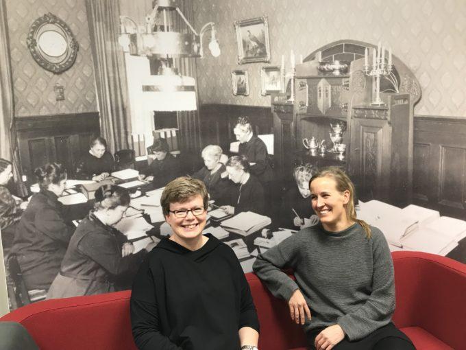 Celian Minna ja Miia istuvat ison historiallisen Celia-valokuvan edessä.