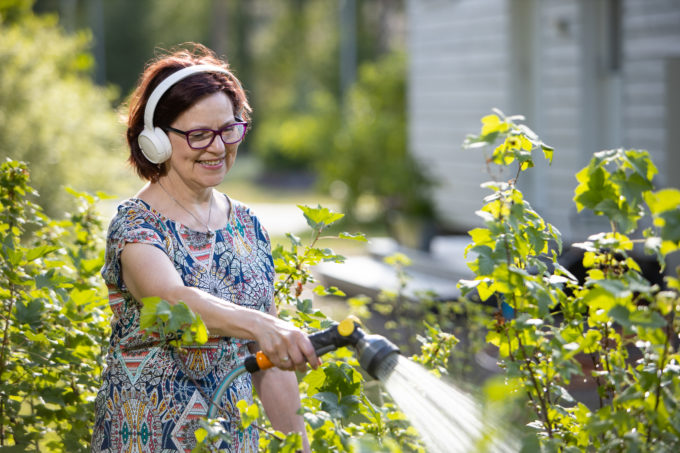 Eläkeläisnainen kuuntelee äänikirjaa ja kastelee kasveja puutarhassa.