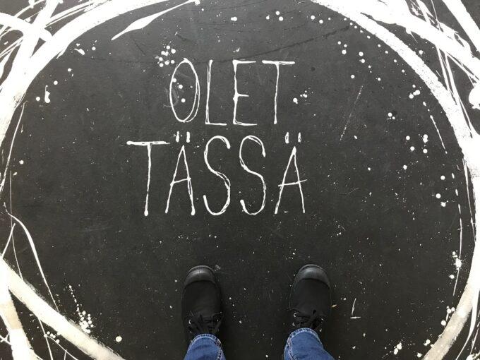 """Henkilön jalat näkyvät, kun hän seisoo paikassa, jonka lattiassa lukee """"Olet tässä""""."""