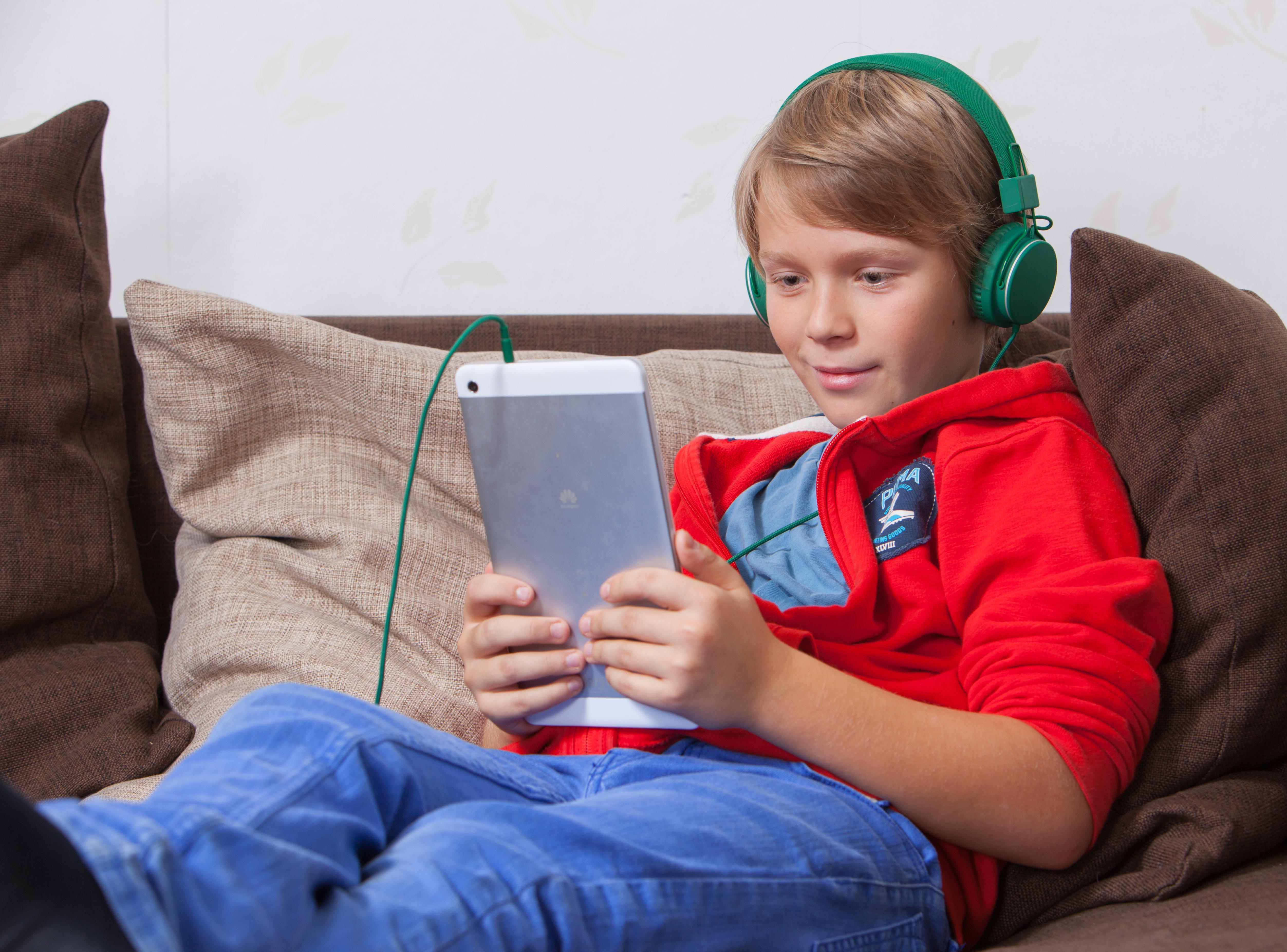 Poika kuuntelee äänikirjaa tabletilla.