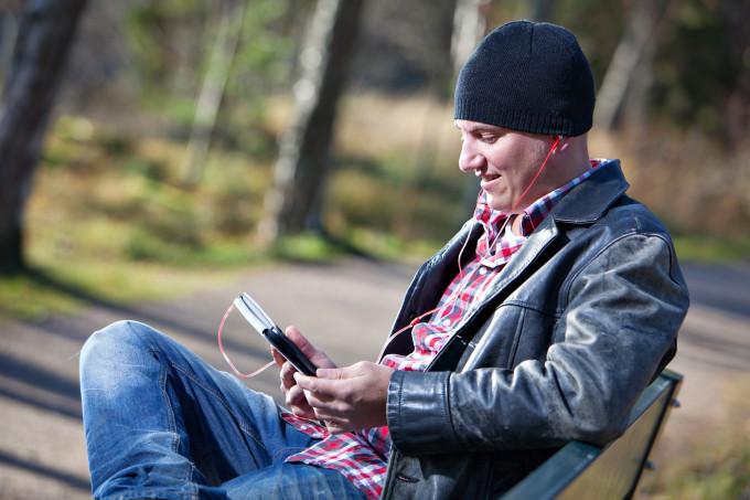 Mies lukee äänikirjaa kännykältään ulkona.