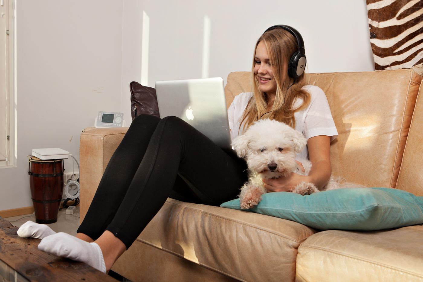 Tyttö istuu koiran kanssa sohvalla läppäri sylissään.