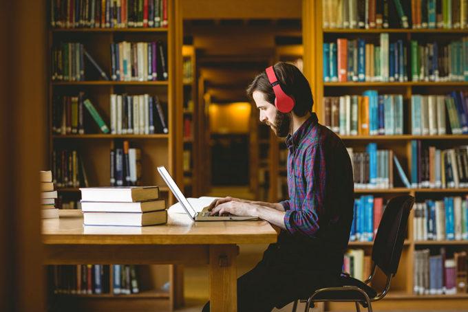 Nuori mies lukee äänikirjaa tietokoneella kirjastossa.