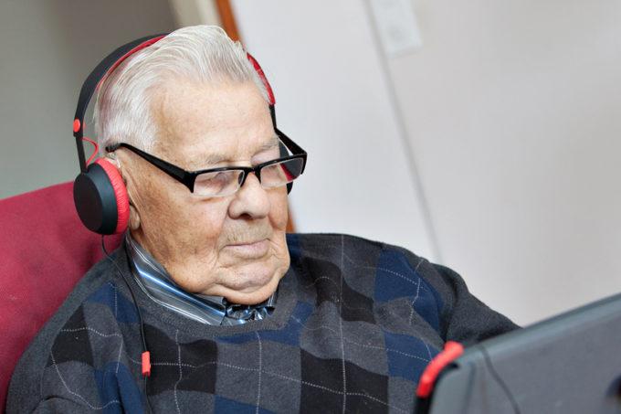 Iäkäs mies kuuntelee äänikirjaa kuulokkeilla.