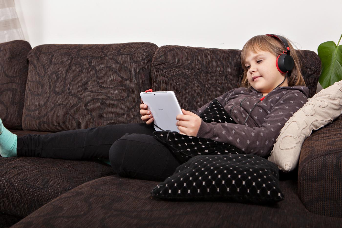 Tyttö kuuntelee äänikirjaa tabletilta.