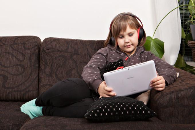 Tyttö kuuntelee kirjaa tabletti kädessä sohvalla.