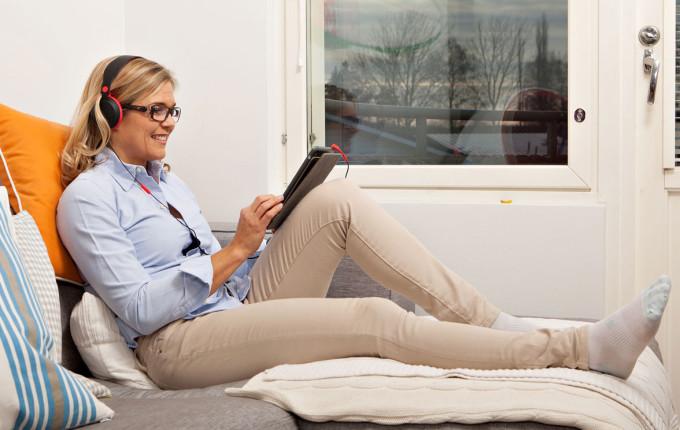 nainen makoilee sohvalla tabletti kädessään.
