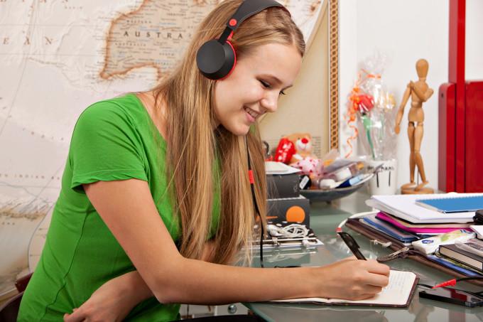Tyttö kirjoittaa muistivihkoon kuulokkeet päässään.