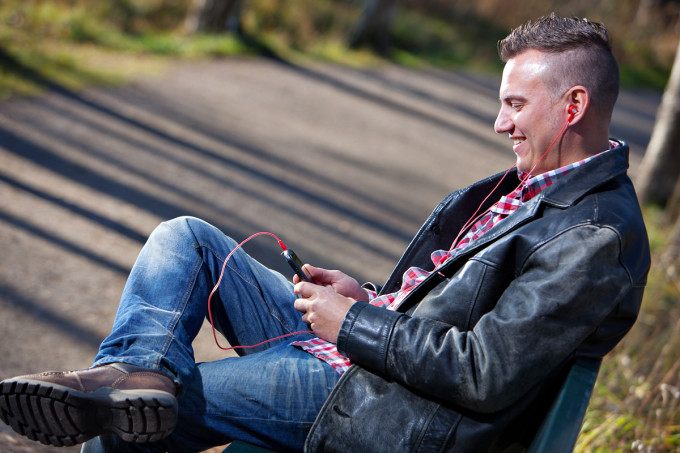 mies istuu penkillä kännykkä kädessään ja kuulokkeet korvillaan.