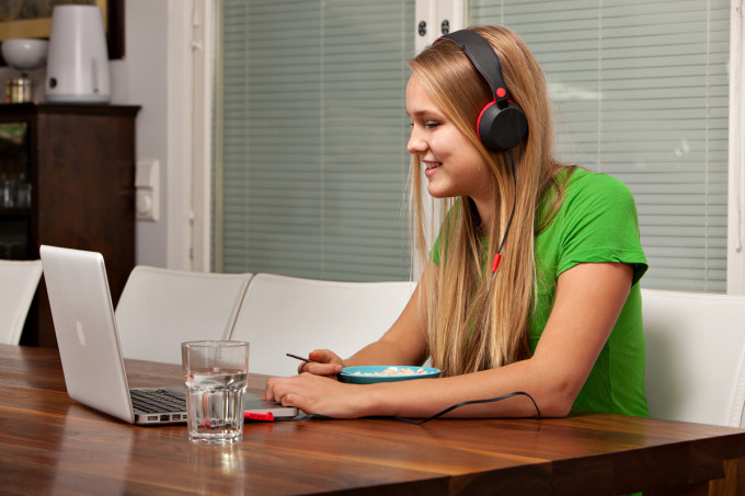 kuvituskuva: tyttö istuu pöydän ääressä tietokoneen edessä