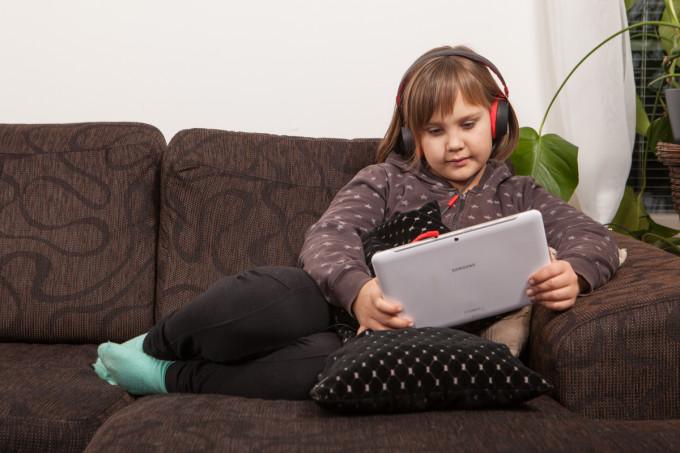 Pieni tyttö kuuntelee äänikirjaa tabletilta ruskealla sohvalla.
