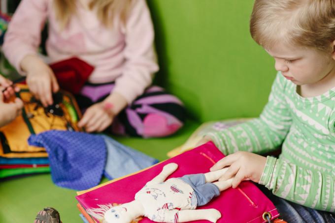Kuvassa koskettelukirjoja tutkivia lapsia.