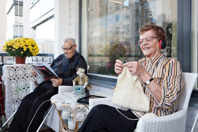 kuvituskuva, jossa ikäihmiset istuvat parvekkeella kuulokkeet korvillaan