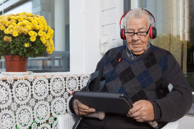 Vanha mies istuu parvekkeella tabletti kädessään ja kuulokkeet korvillaan