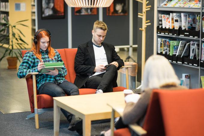 Kirjaston nuoria asiakkaita istuu sohvilla pöydän ympärillä.