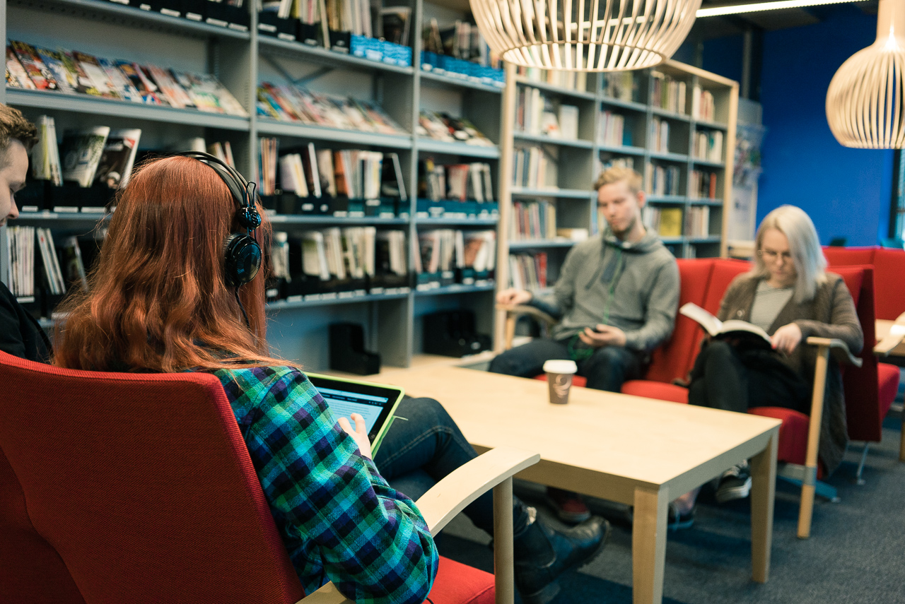 Kirjaston nuoria asiakkaita istuu penkeillä pöydän ääressä. Yksi katsoo tablettia kuulokkeet korvillaan, toinen tutkii kännykkää ja kolmas lukee kirjaa.