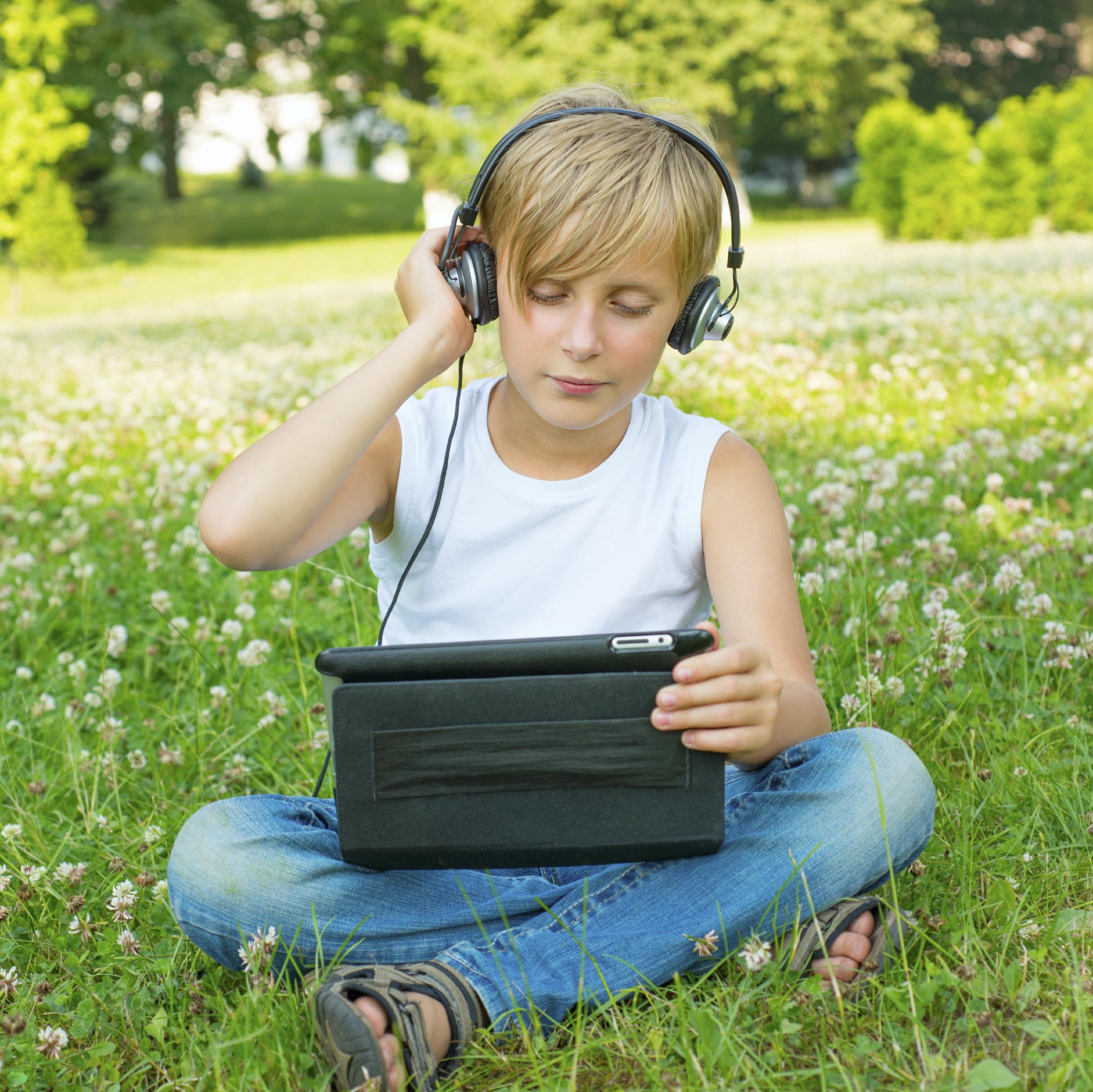 Nuori istuu kedolla kuulokkeet päässä ja tabletti sylissä