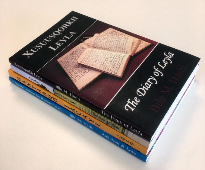 Neljä somalinkielistä kirjaa pinossa.