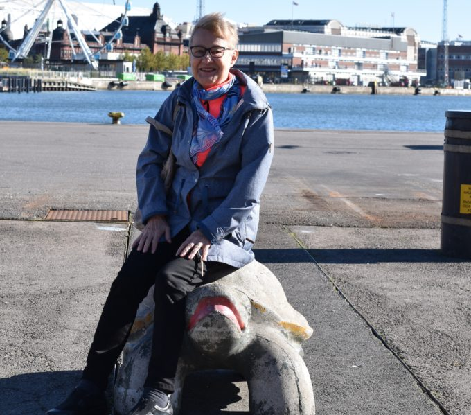 Marja-Liisa istuu betonikilpikonnan päällä