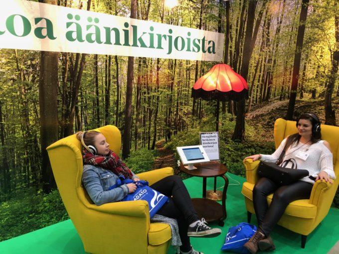 Kuvassa kaksi nuorta naista istuu nojatuoleissa ja kuuntelee äänikirjaa.