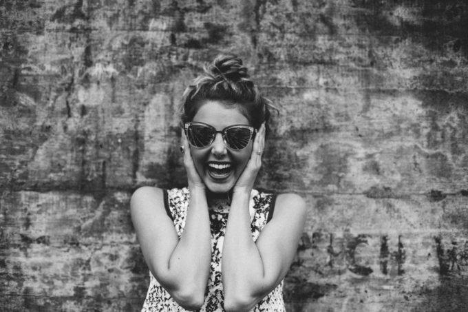 Hyvin innostunut hymyilevä nainen kädet korvilla