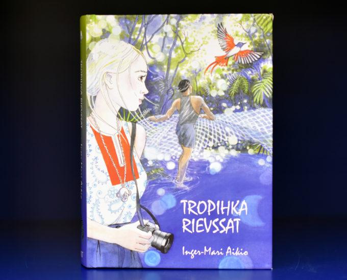 Kuvassa Inger-Mari Aikion painotuore kirja Tropihka rievssat. Sademetsäteemaisessa kannessa tyttö katsoo kamera kädessä miestä, joka seisoo joessa verkon kanssa. Kaunis lintu lentää kohti valoa.