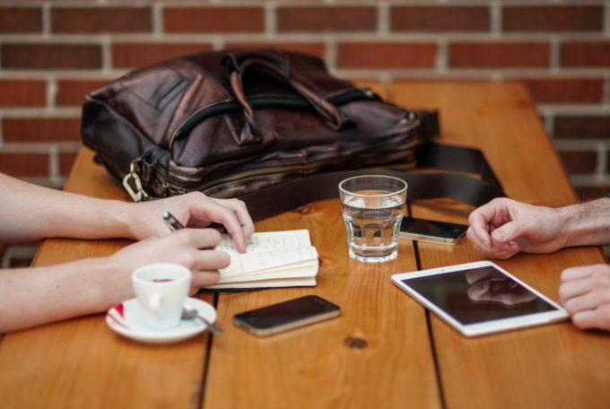 Pöydällä tabletti, puhelin, muistikirja, laukku ja kahden opiskelijan kädet.