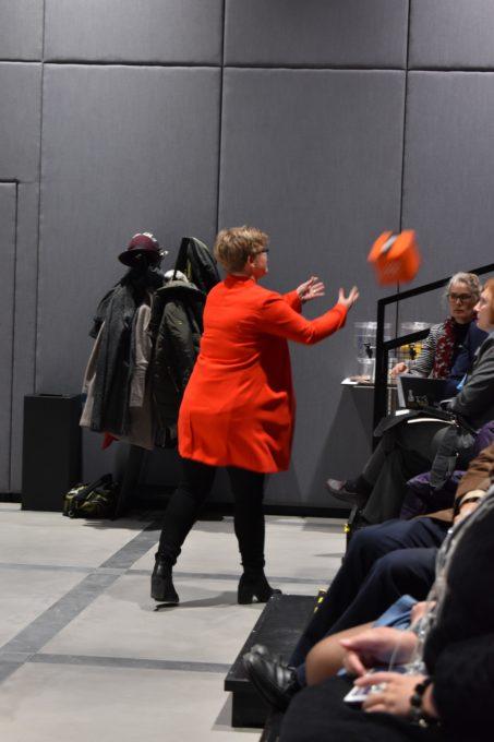 Punaiseen pukeutunut nainen heittää kuution muotoista oranssia pehmeää mikrofonia yleisöön.