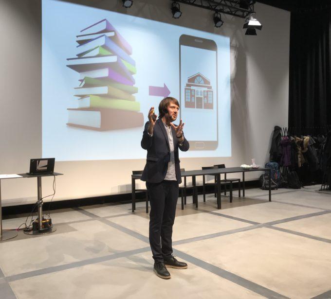 Jesper lavalla, taustalla kuvassa kirjoja, joista on nuoli kännykkään.