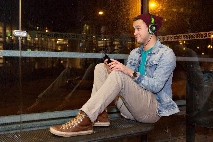 Mannen lyssnar på en talbok vid ett busshållplats.